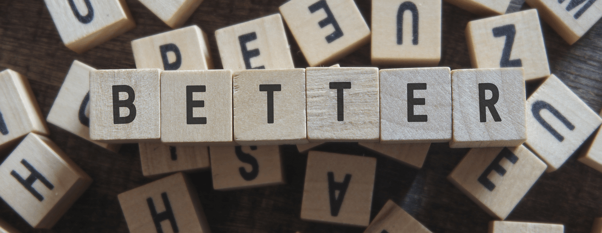 The word better spelled out in wooden blocks on top of jumbled wooden blocks