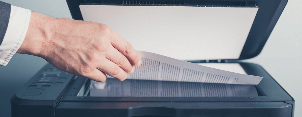 Hand of a businessman placing a document on a flatbed scanner in preparation for copying it