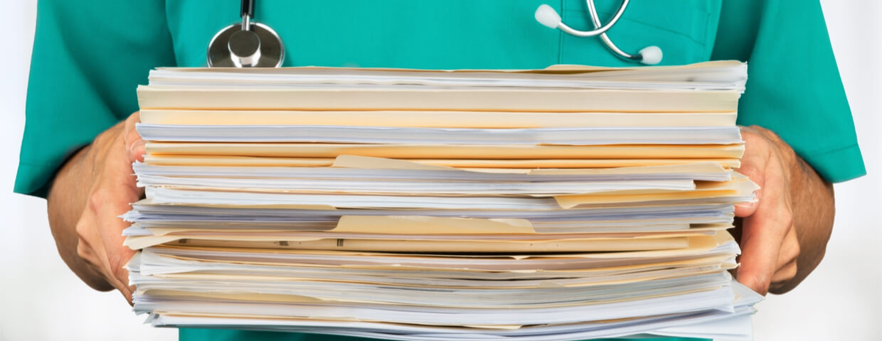 Healthcare worker holding stack of documents