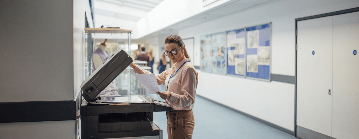 teacher standing at a multifunction printer in a school hallway, managed print services for education concept